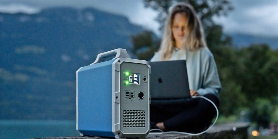 Mujer trabajando y cargando su portátil por generador solar.